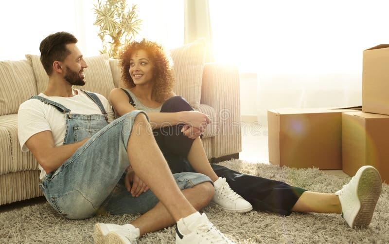 Pareja casada feliz que se sienta en la alfombra en un nuevo apartamento fotos de archivo libres de regalías