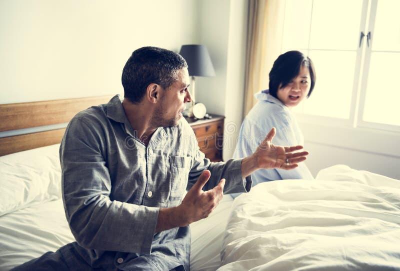 Pareja casada infeliz que discute en una cama foto de archivo libre de regalías