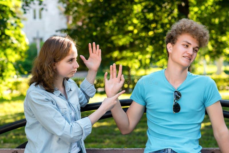 Pareja casada jóvenes En verano en el parque en naturaleza La muchacha reprende al individuo Emociones de los insultos de la desc foto de archivo