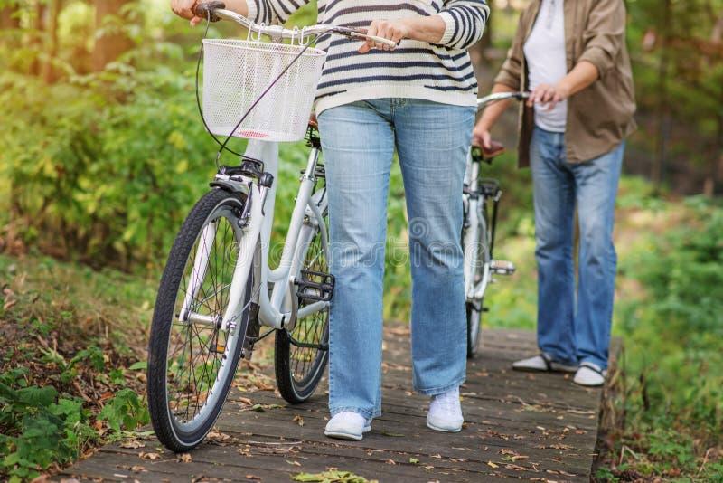 Pareja casada madura que camina con las bicicletas foto de archivo libre de regalías