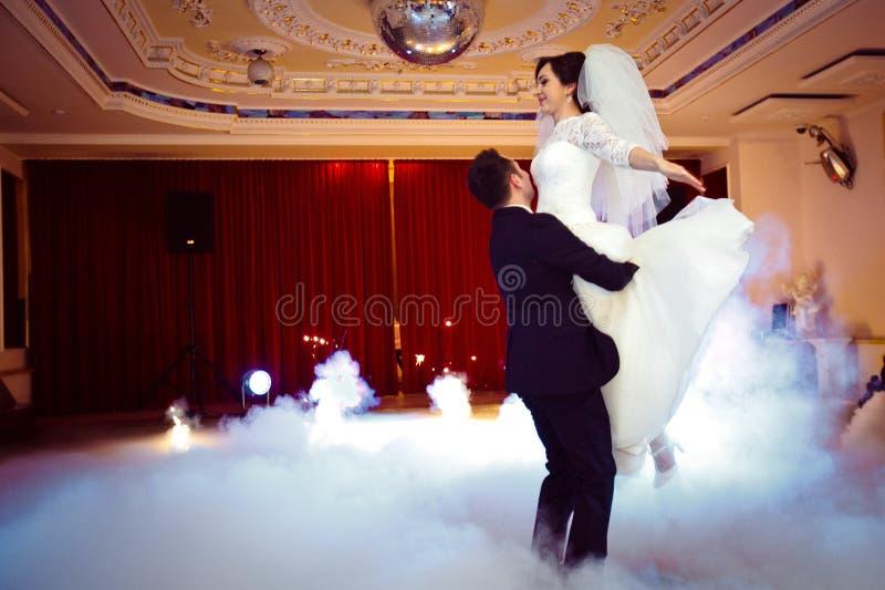 Pareja casada magnífica elegante feliz que realiza la primera danza con humo pesado y fuegos artificiales en un restaurante elega fotografía de archivo