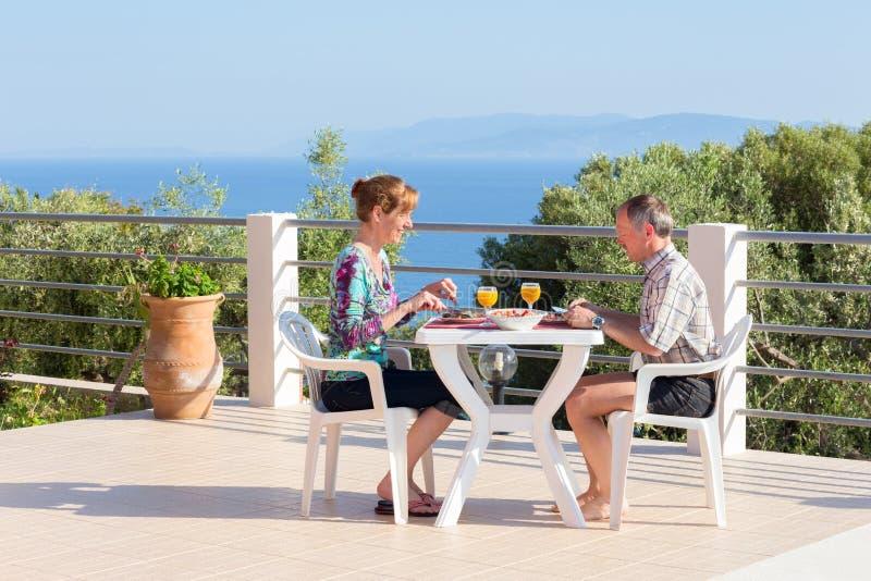 Pareja casada que come en la tabla en terraza cerca del mar foto de archivo