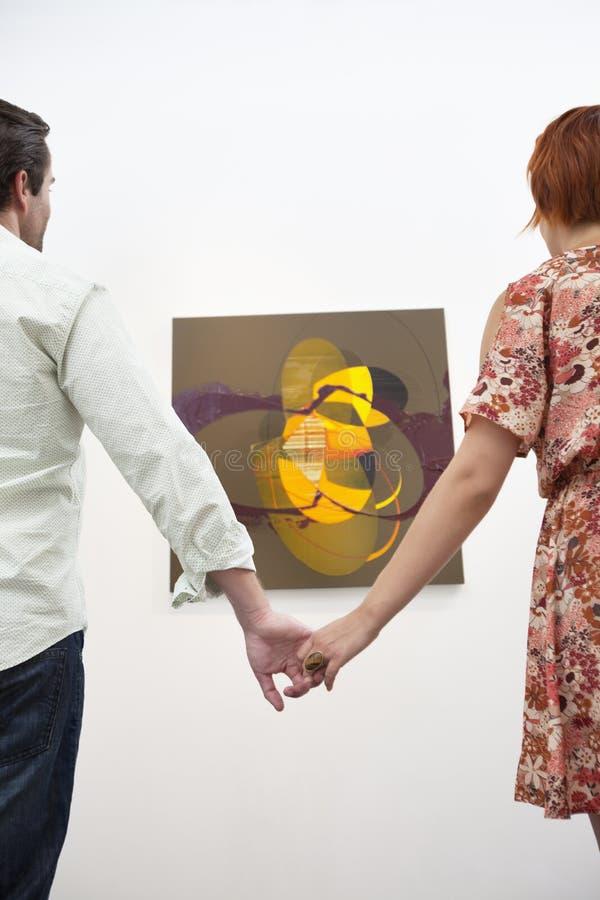 Pareja casada que lleva a cabo las manos delante de la pintura en galería de arte fotografía de archivo