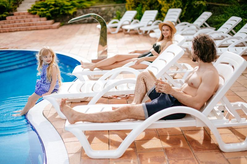 Pareja con la hija el vacaciones usando la tableta digital cerca de la piscina foto de archivo libre de regalías