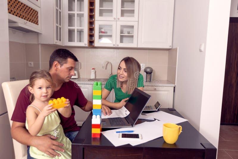 Pareja con la hija que trabaja de hogar usando el ordenador port?til imagen de archivo