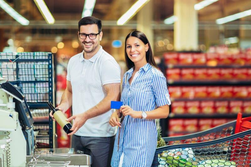 Pareja con tarjeta bancaria comprando comida en una tienda de comestibles o en un supermercado autocobrando fotografía de archivo libre de regalías