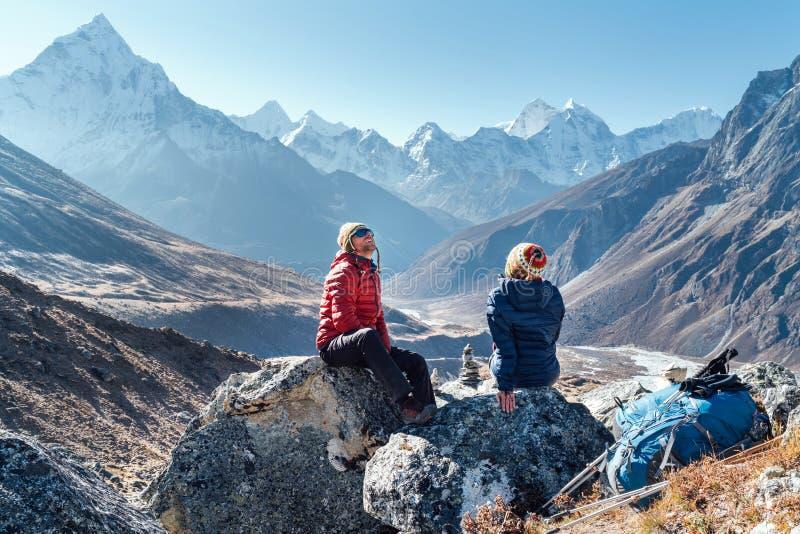 Pareja Cuta descansando en la ruta de senderismo del campamento base del Everest cerca de Dughla 4620m Hombre y mujer disfrutando imagen de archivo libre de regalías