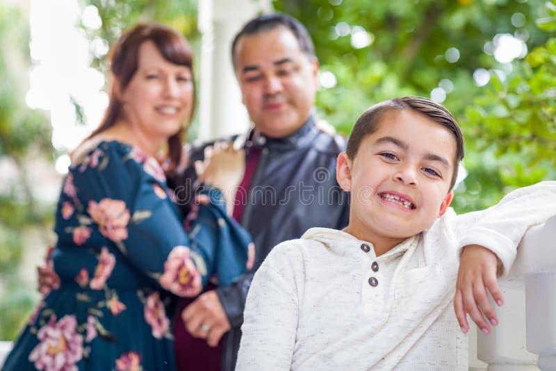 Pareja de la raza mixta que se coloca detrás de hijo joven fotografía de archivo
