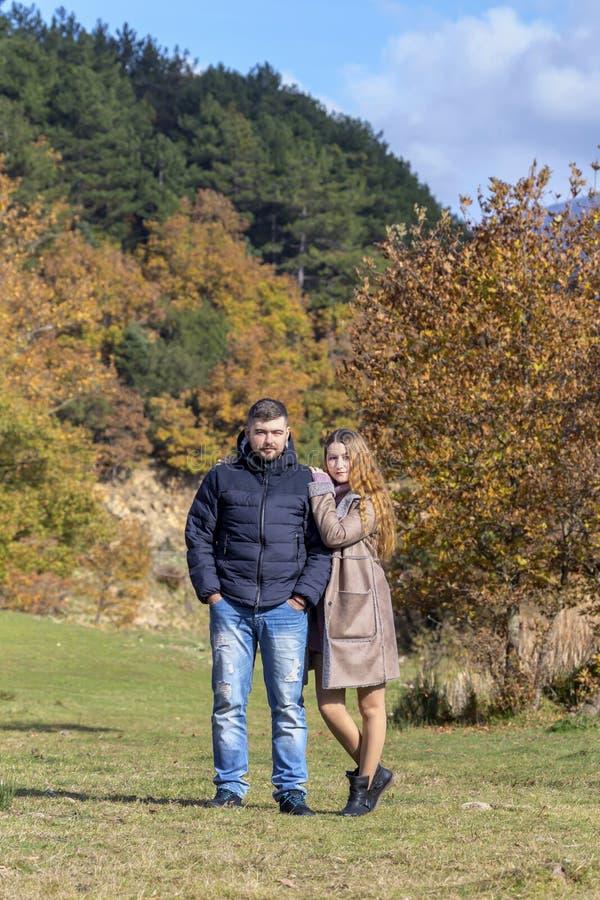 Pareja de matrimonios hermosa joven contra la perspectiva del bosque del otoño en un primer del día soleado fotografía de archivo