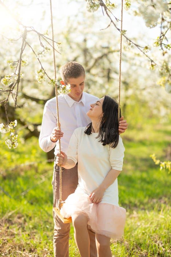 Pareja de matrimonios joven, en un oscilación en un jardín florecido o un parque Con gusto, humor del amor, de la primavera y del fotos de archivo