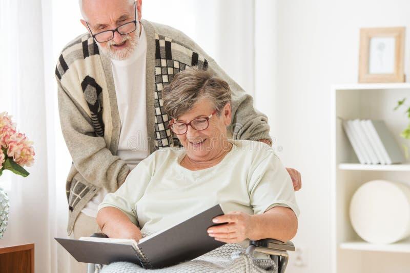 Pareja de matrimonios mayor feliz con el álbum de foto en la clínica de reposo imagenes de archivo
