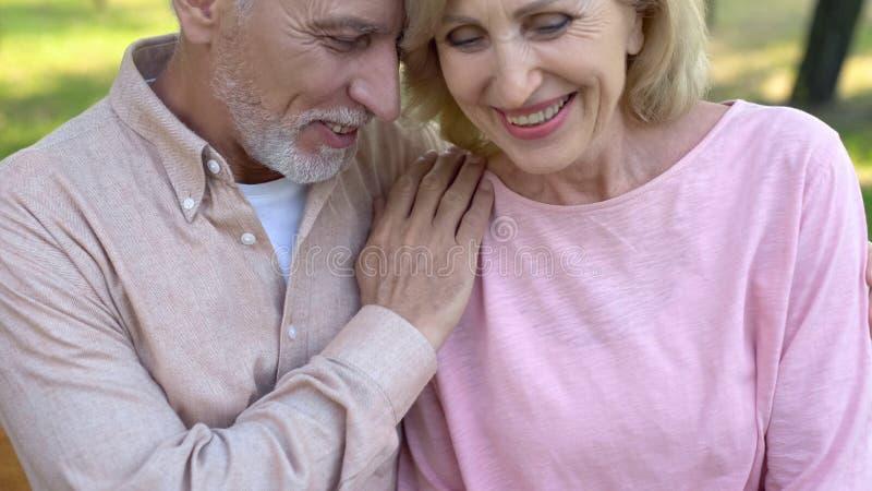 Pareja de matrimonios que disfruta de la fecha al aire libre, riendo junto, proximidad de la relación fotografía de archivo libre de regalías