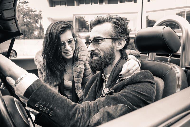 Pareja de moda Hipster lista para un viaje por carretera con un carro de cabriolet - Jóvenes alegres sonriendo y divirtiéndose - imagen de archivo libre de regalías