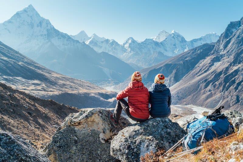Pareja descansando en la ruta de senderismo del campamento base del Everest cerca de Dughla 4620m Mochileros dejaron mochilas y p fotografía de archivo libre de regalías