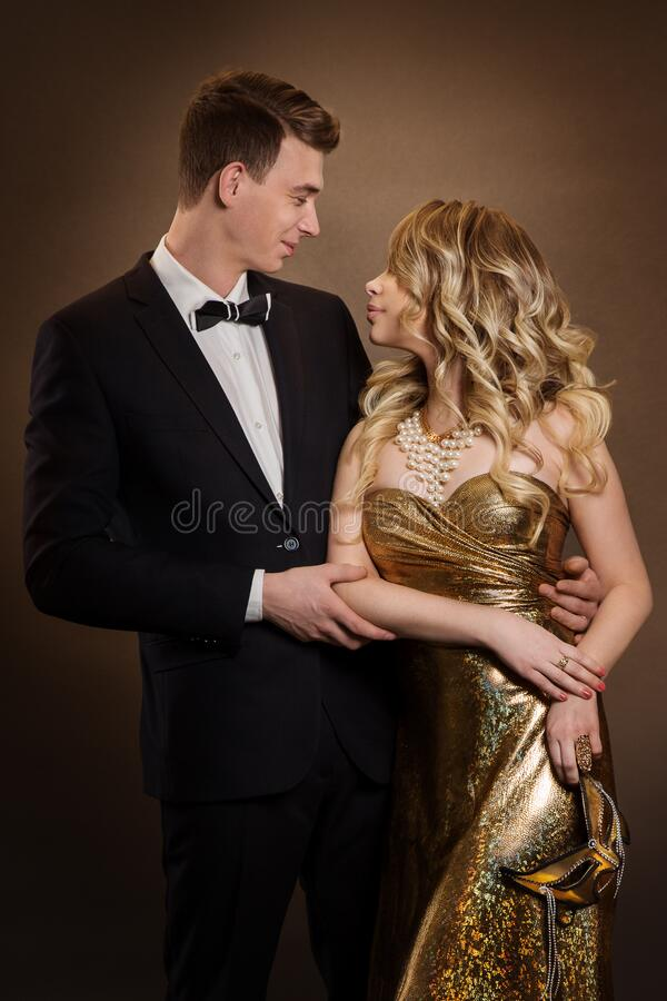 Pareja elegante, mujer de moda con vestido de oro, hombre elegante con traje de Tuxedo imagen de archivo