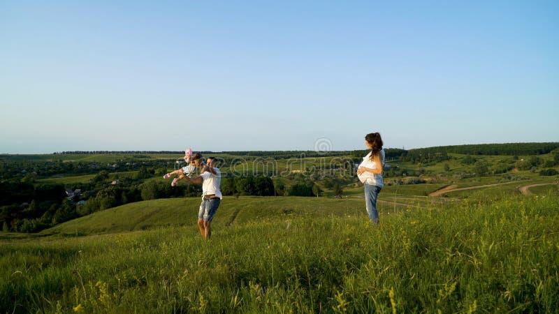 Pareja embarazada con la hija del niño que camina en los campos verdes que tienen tiempo libre foto de archivo