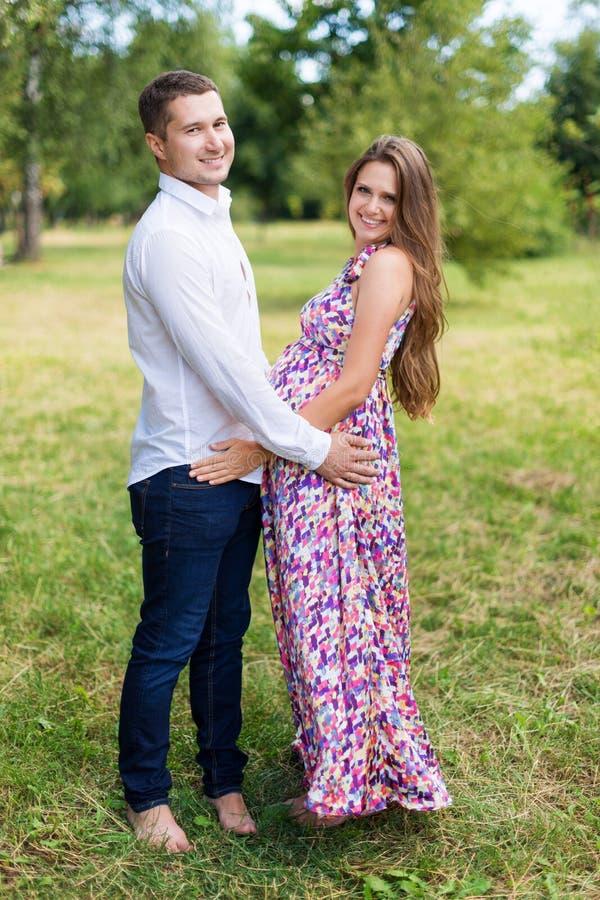 Pareja embarazada hermosa feliz junto contando con a un niño Hombre y mujer que caminan en el parque Comparta el amor y a la fami imágenes de archivo libres de regalías
