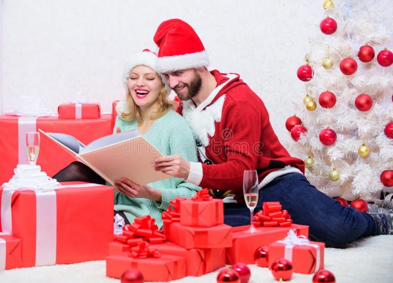 Pareja enamorada disfruta de la Navidad La familia cuddle bebe champán cerca del árbol de Navidad mientras mira el álbum de fotos imágenes de archivo libres de regalías
