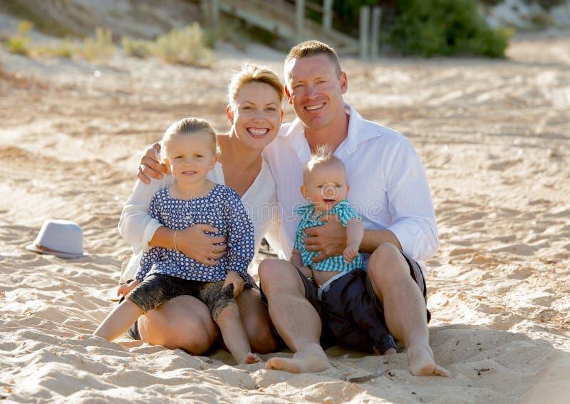 Pareja feliz de la familia que se sienta en la arena de la playa con el hijo y la hija del bebé fotografía de archivo libre de regalías