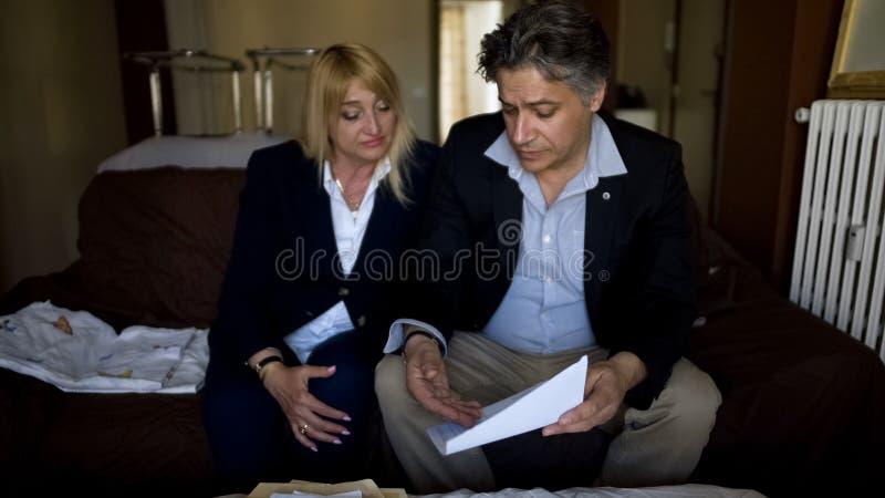 Pareja fusionada que comprueba los documentos, decidiendo vender negocio debido a deudas foto de archivo
