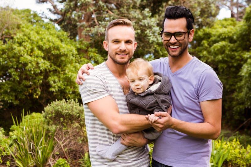 Pareja gay sonriente con el niño fotografía de archivo