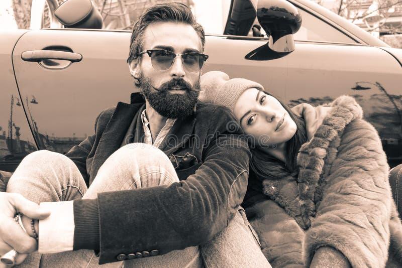 Pareja hipster de moda sentada fuera del carro de cabriolet - Amantes que viajan por Europa para un viaje por carretera - Enfoque foto de archivo