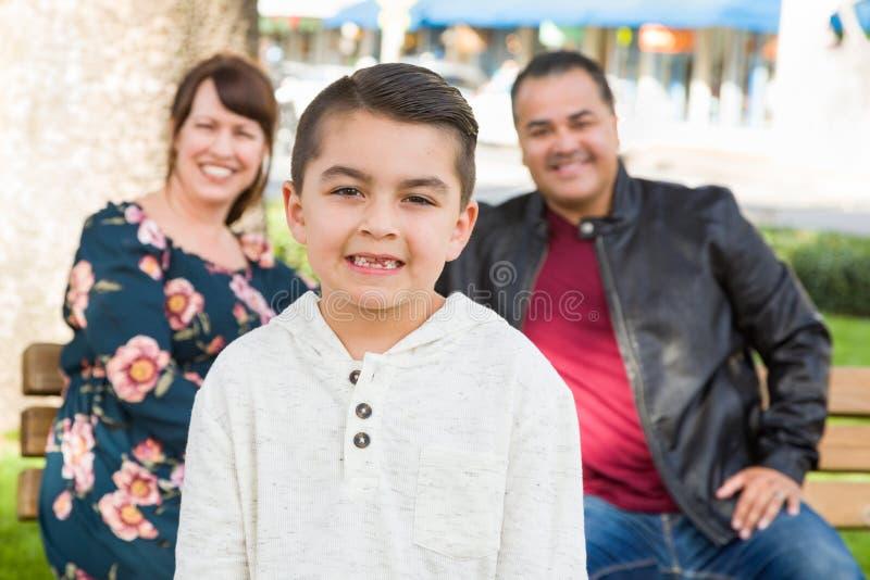 Pareja joven de la raza mixta detrás de su hijo en un banco de parque imagenes de archivo