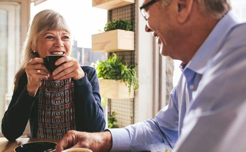 Pareja jubilada sonriente tomando café en un café foto de archivo libre de regalías