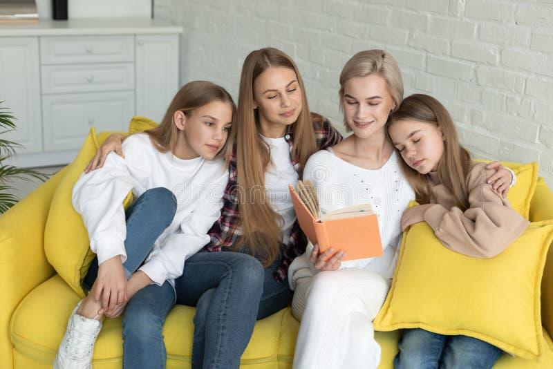 Pareja lesbiana en ropa casual con sus hijas que leen un libro imagen de archivo libre de regalías