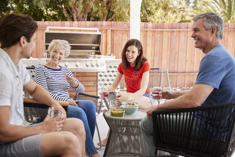 Pareja mayor y niños adultos que hablan en su patio trasero imagenes de archivo