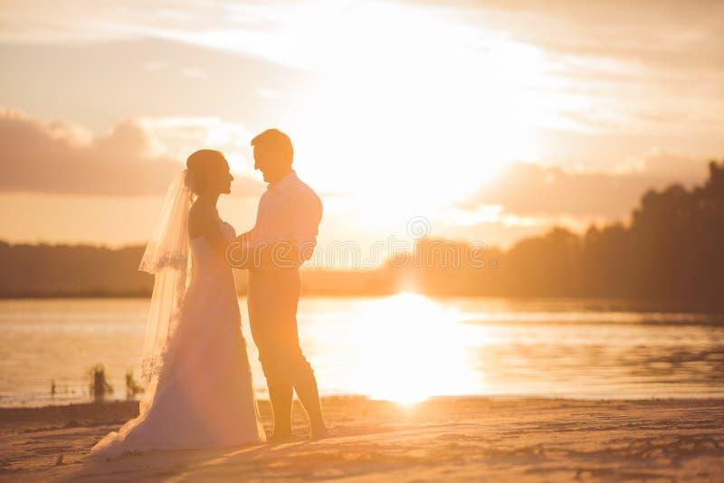 Pareja nuevamente casada en el río con puesta del sol fotos de archivo