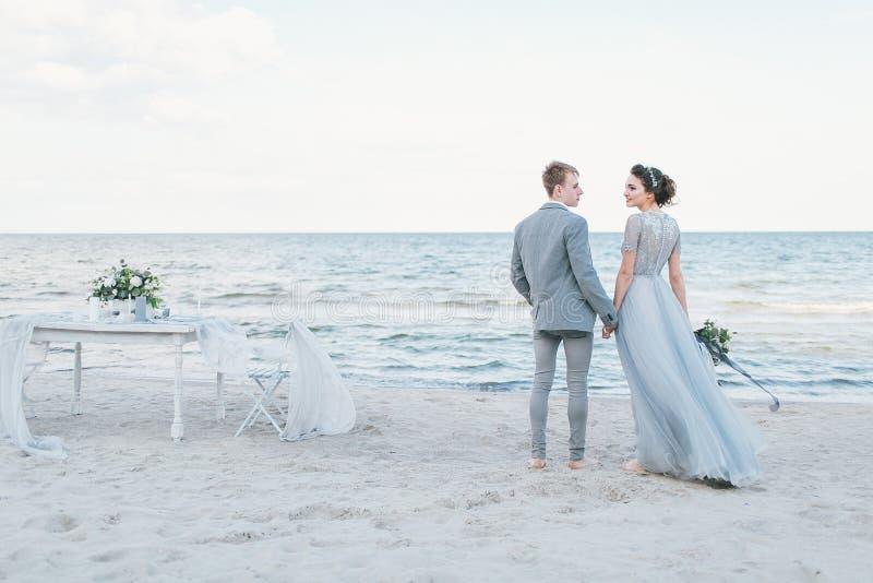 Pareja nuevamente casada que lleva a cabo las manos por el mar fotografía de archivo