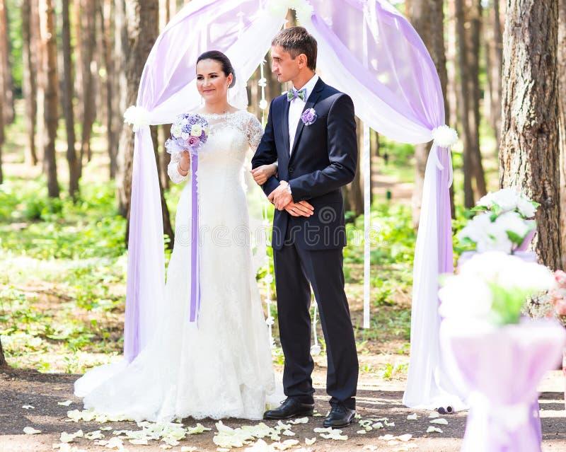 Pareja que consigue casada en una ceremonia de boda al aire libre, fotografía de archivo libre de regalías