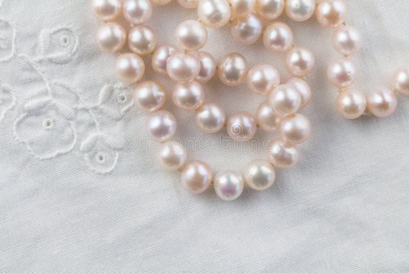 Parelhalsband op witte geborduurde linnenachtergrond - hoogste mening van koord van roze parels royalty-vrije stock fotografie
