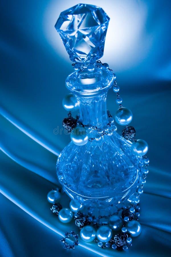 Parels en fles op blauwe achtergrond 3 stock afbeeldingen