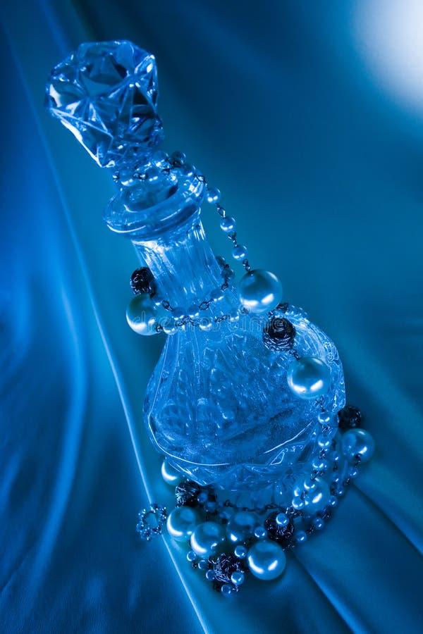 Parels en fles op blauwe achtergrond royalty-vrije stock afbeeldingen