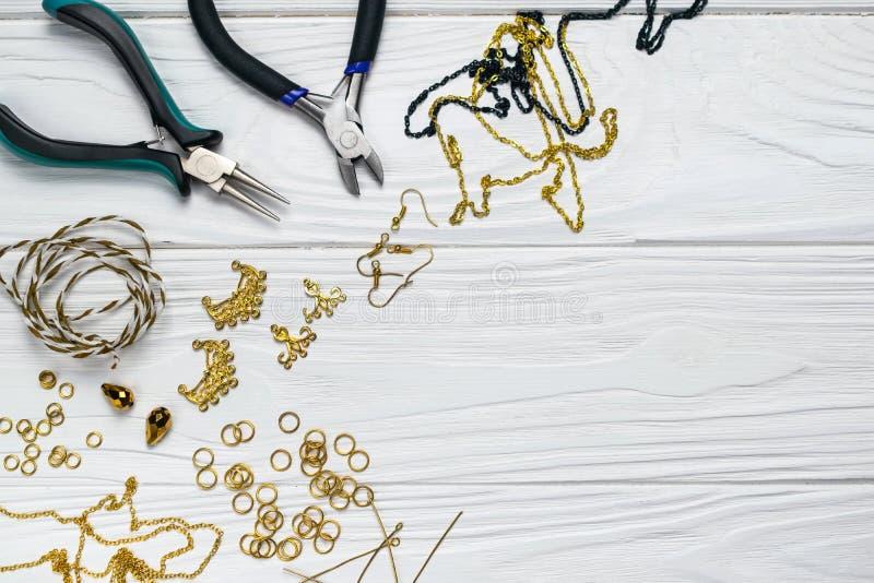 Parelt de met de hand gemaakte de ambachtsamenstelling van juwelenbevindingen met buigtang embelilshments op witte houten achterg royalty-vrije stock fotografie