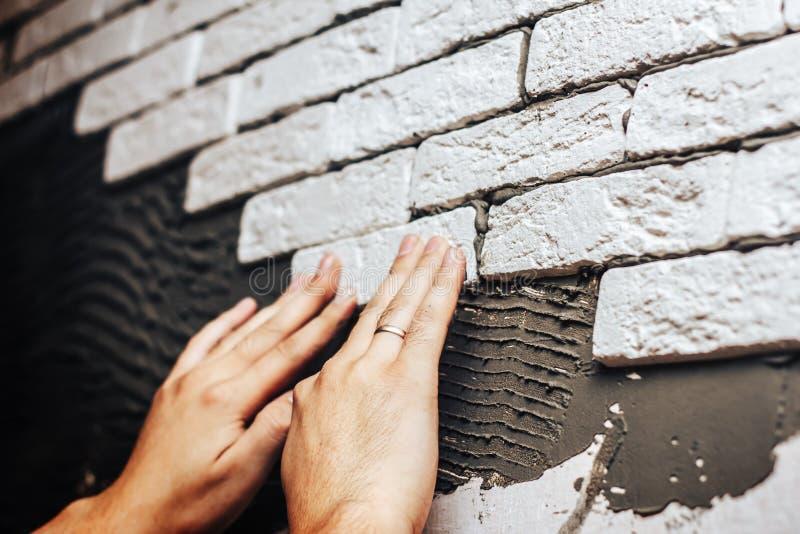 Parement des tuiles décoratives de mur, travailleurs faisant le mur de briques image stock