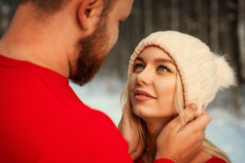 Paren i den röda tröjan i vintern i den lyckliga kramromanens för skog arkivbild