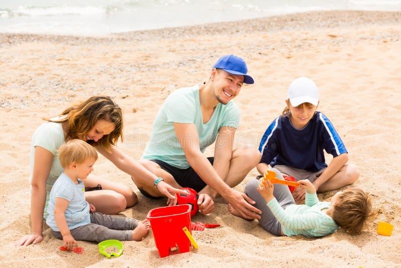 Parens felizes com as três crianças na praia imagem de stock royalty free