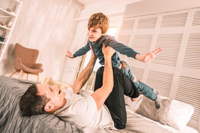 Parent aimant supportant soigneusement son enfant au-dessus de lui photos libres de droits