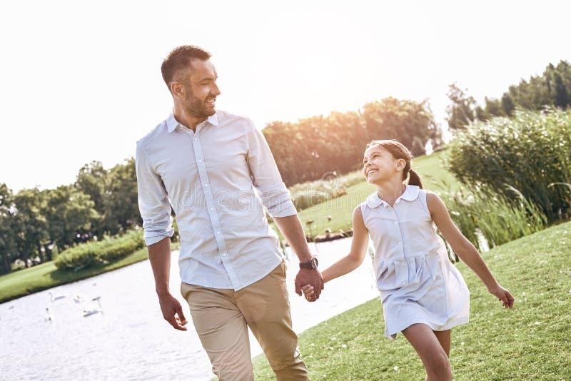 Parent célibataire, père et fille marchant sur HOL herbeux de champ photos stock