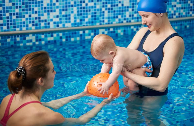 Parent and child having leisure time in swimming pool using inflatable toys for water fun. Child development. Side view stock photography