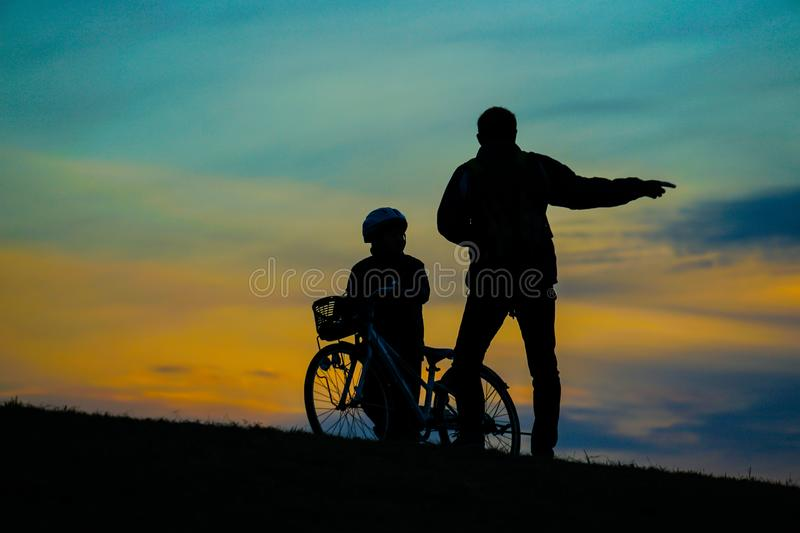 Parent and child silhouette standing in the sunset of the hill. Shooting location :  Chofu, Tokyo royalty free stock photos