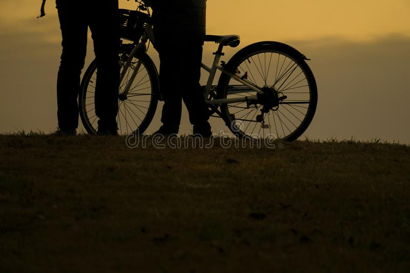 Parent and child silhouette standing in the sunset of the hill. Shooting location :  Chofu, Tokyo royalty free stock image