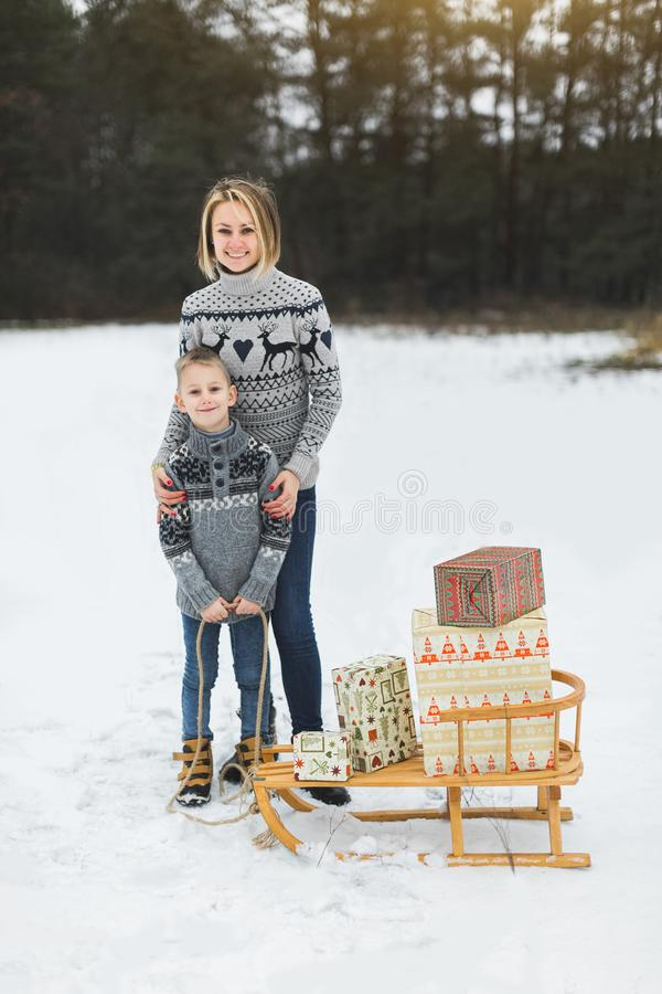 Parent and child with sleigh, winter sledding, outdoor activity. Christmas vacation, family, son and mother with. Decorated wooden sledge in forest. Playing royalty free stock photo