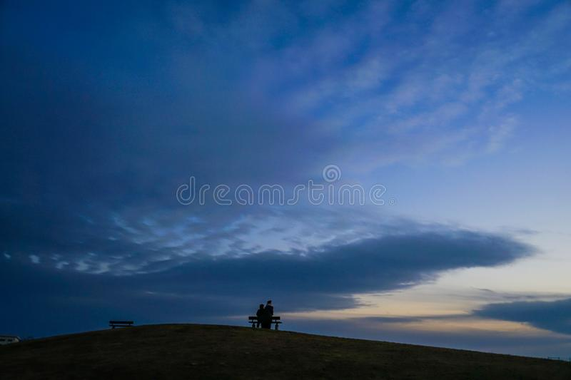 Parent and child to sit in the sunset of the hills of the bench. Shooting location :  Yokohama-city kanagawa prefecture stock image