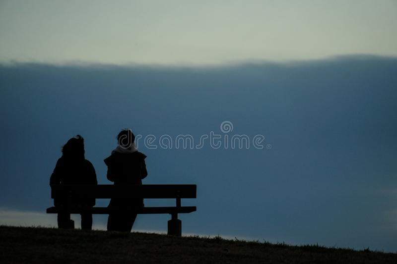 Parent and child to sit in the sunset of the hills of the bench. Shooting location :  Chofu, Tokyo royalty free stock images