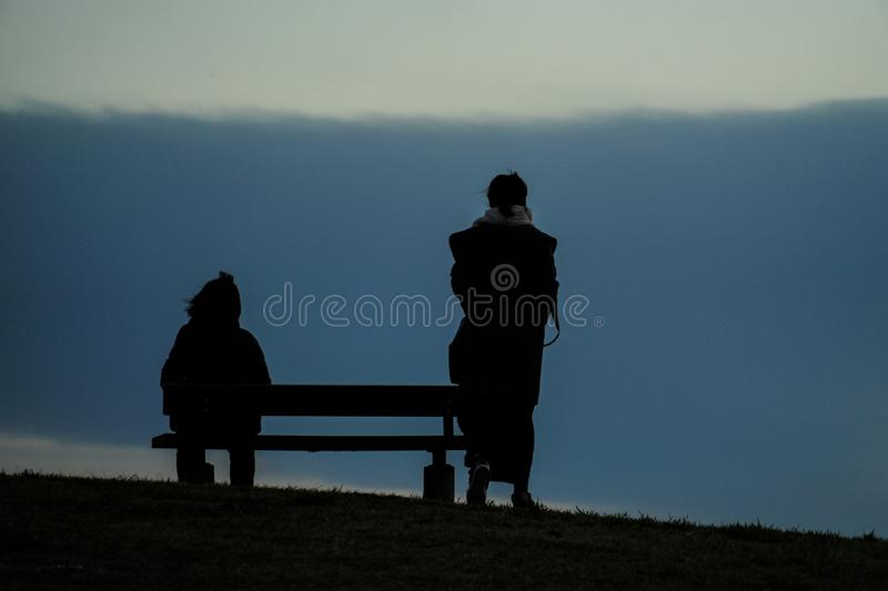 Parent and child to sit in the sunset of the hills of the bench. Shooting location :  Chofu, Tokyo stock images
