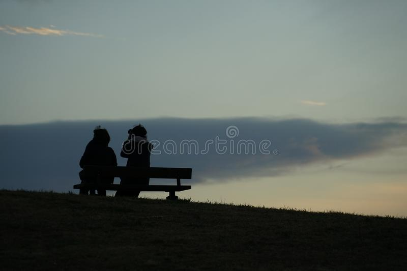 Parent and child to sit in the sunset of the hills of the bench. Shooting location :  Chofu, Tokyo royalty free stock photography